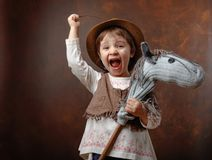 Cute little girl dressed like a cowboy playing with a homemade h. Orse. Expressive facial expressions. Copy space for your text Royalty Free Stock Images