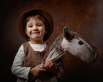 Cute little girl dressed like a cowboy playing with a homemade h. Orse. Expressive facial expressions Royalty Free Stock Image