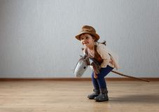 Cute little girl dressed like a cowboy playing with a homemade h. Orse. Expressive facial expressions Stock Photography