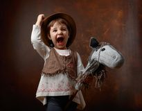 Cute little girl dressed like a cowboy playing with a homemade h. Orse. Expressive facial expressions Stock Images