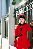 Cute little girl dressed in old-style coat posing on the street. Sunny day Stock Photo