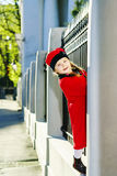 Cute little girl dressed in old-style coat posing on the street. Sunny day Royalty Free Stock Photos