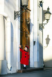 Cute little girl dressed in old-style coat posing on the street. Sunny day Stock Image