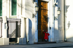 Cute little girl dressed in old-style coat posing on the street. Sunny day Royalty Free Stock Image