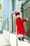Cute little girl dressed in old-style coat posing on the street. Sunny day Royalty Free Stock Images