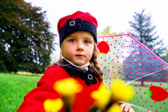 Cute little girl dressed in red coat and hat on green grass field royalty free stock images