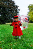 Cute little girl dressed in red coat and hat on green grass fiel Royalty Free Stock Photos