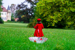 Cute little girl dressed in red coat and hat on green grass fiel Royalty Free Stock Image