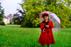 Cute little girl dressed in red coat and hat on green grass fiel Royalty Free Stock Images