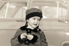Cute little girl dressed in retro coat posing near oldtimer car Stock Photos