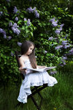 Cute little girl, dressed in a white dress,  sitting in the garden in the park and reading a book. green and blooming lilacs Stock Photo
