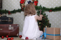 Cute little girl dresses up Christmas tree Stock Photos
