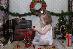 Cute little girl dresses up Christmas tree Royalty Free Stock Photography