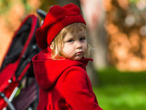 Cute little girl dressing in red coat Stock Photos