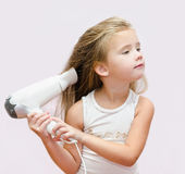 Cute little girl dries hair Royalty Free Stock Photo