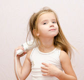 Cute little girl dries hair Royalty Free Stock Photos