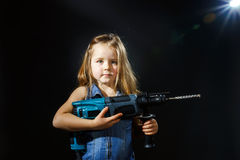 Cute little girl with drilling machine in her hands Stock Images