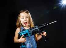 Cute little girl with drilling machine in her hands Stock Image