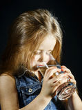 Cute little girl drinking clear water Royalty Free Stock Image
