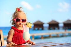 Cute little girl drinking cocktail on tropical Stock Image