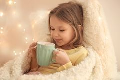 Cute little girl drinking hot chocolate. At home Stock Photo