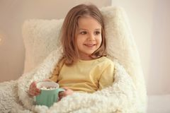 Cute little girl drinking hot chocolate. At home Stock Image