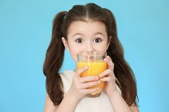 Cute little girl drinking juice. On color background Stock Photography