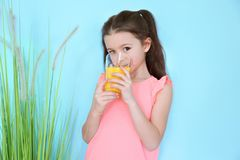 Cute little girl drinking juice. On color background Stock Photo