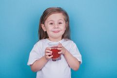 Cute little girl drinking juice from glass royalty free stock images