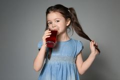 Cute little girl drinking juice. On grey background Stock Image