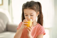 Cute little girl drinking juice. At home Royalty Free Stock Image