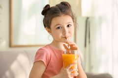 Cute little girl drinking juice. At home Stock Images