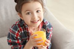 Cute little girl drinking juice while sitting on sofa at home. Closeup Stock Photos