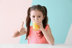 Cute little girl drinking juice while sitting at table. On color background Royalty Free Stock Photo