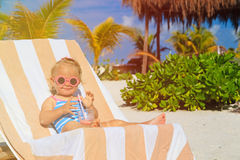 Cute little girl drinking juice on tropical beach Royalty Free Stock Photo