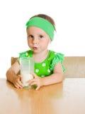 Cute little girl drinking milk from big glass Stock Photos