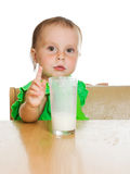 Cute little girl drinking milk from big glass Royalty Free Stock Photos