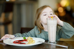 Cute little girl drinking milk coctail Stock Photos