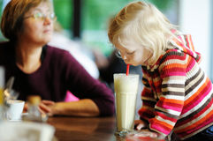 Cute little girl drinking milk coctail Royalty Free Stock Images