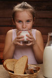 Cute little girl is drinking milk Stock Photo