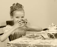 Cute little girl drinking tea at the old table. Stock Photos