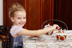 Cute little girl drinking tea at the old table. Royalty Free Stock Images