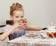 Cute little girl drinking tea at the old table. Royalty Free Stock Photos