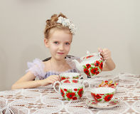 Cute little girl drinking tea at the old table. Stock Photography