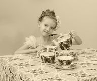 Cute little girl drinking tea at the old table. Stock Photo