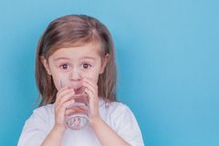 Cute little girl drinking water from glass. On blue background royalty free stock photography