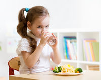 Cute little girl drinking water. Sitting at table in nursery Stock Images