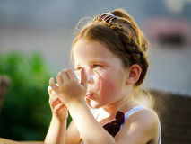 Cute little girl drinking water on the sun Royalty Free Stock Photo