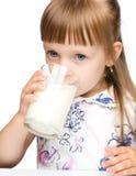 Cute little girl drinks milk. Isolated over white Stock Photos