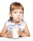 Cute little girl drinks milk using drinking straw. Over white Royalty Free Stock Photo